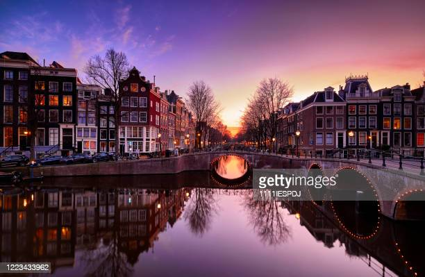 amsterdam canals and typical canal houses at dusk - amsterdam stock pictures, royalty-free photos & images