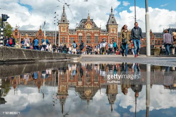 Amsterdam Centraal station with its reflection with busy locals and tourist walking in the Dutch capital Amsterdam The Netherlands during a summer...