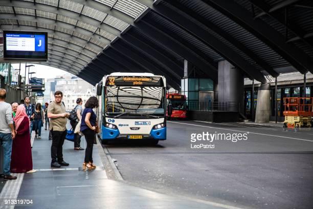 Amsterdam centraal trein station interieur. Busstation binnen het station met mensen die wachten op de bus.