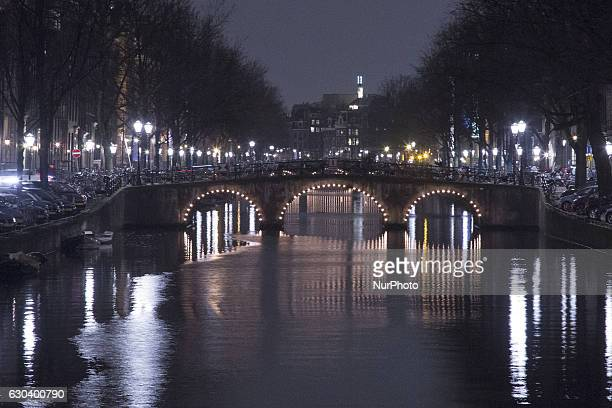Amsterdam city before Christmas and New Year's Eve decorated with thousands of light bulds near the canals on the bridge on the water and all over...