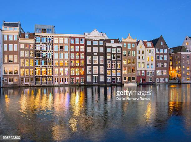 Amsterdam city buildings reflected in a canal at sunset The Netherlands