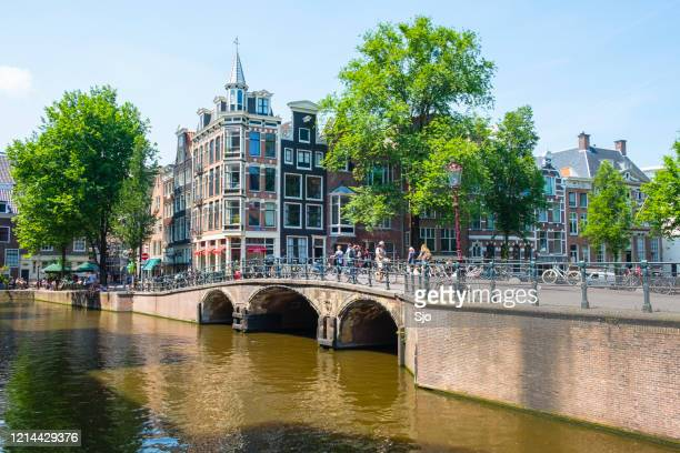 """amsterdam city canal with historical buildings in the netherlands with bicycles parked next to a canal in amsterdam - """"sjoerd van der wal"""" or """"sjo"""" stock pictures, royalty-free photos & images"""