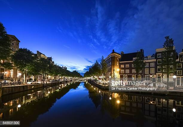 Amsterdam cityscape illuminated at dusk and reflected on canal waters, the Netherlands