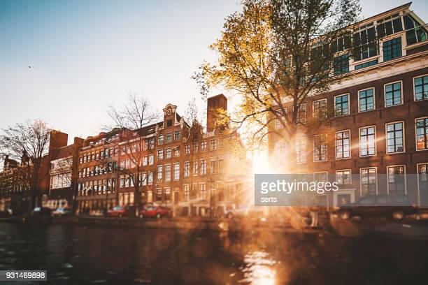 amsterdam cityscape with canal and bridges in netherlands - ship front view stock photos and pictures