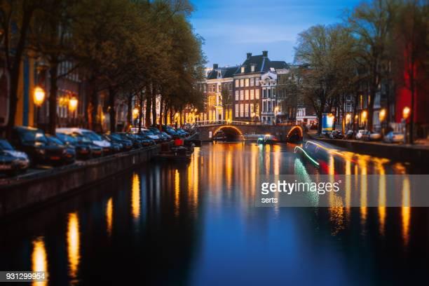 Stadtbild von Amsterdam mit beleuchteten Grachtenhäuser und Boote in der Abenddämmerung