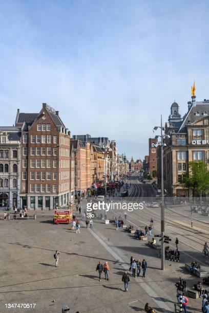 "amsterdam dam square and damrak street with people walking on the street - ""sjoerd van der wal"" or ""sjo"" stockfoto's en -beelden"