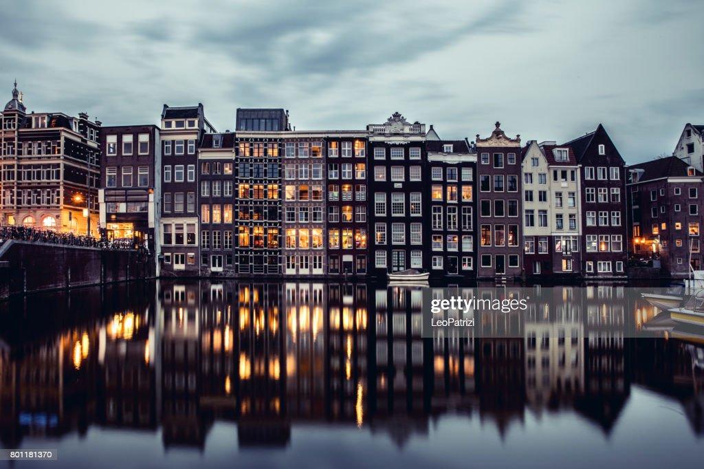 Amsterdam alberga reflexiones en la noche en el agua del canal : Foto de stock