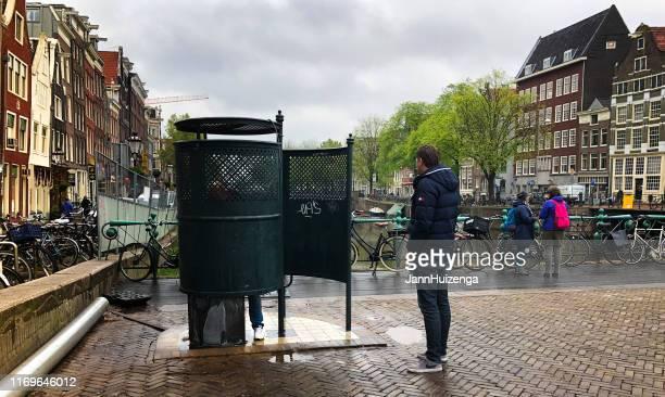 amsterdam, países bajos: hombre esperando al aire libre urinal - barrio rojo fotografías e imágenes de stock