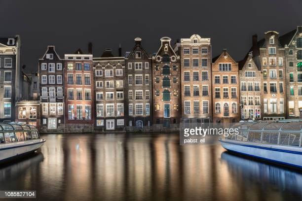 amsterdam skyline old buildings waterfront damrak - canale foto e immagini stock