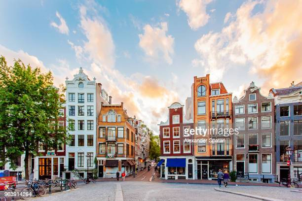 amsterdam skyline with traditional dutch houses during sunset, holland, netherlands - stadsstraat stockfoto's en -beelden