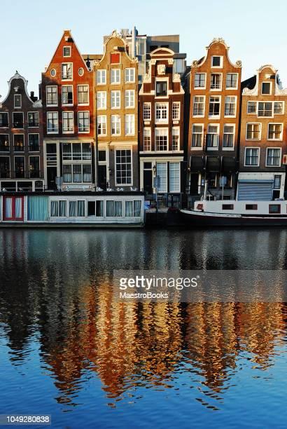 Amsterdam gekanteld en scheve huizen weerspiegeld op het water.