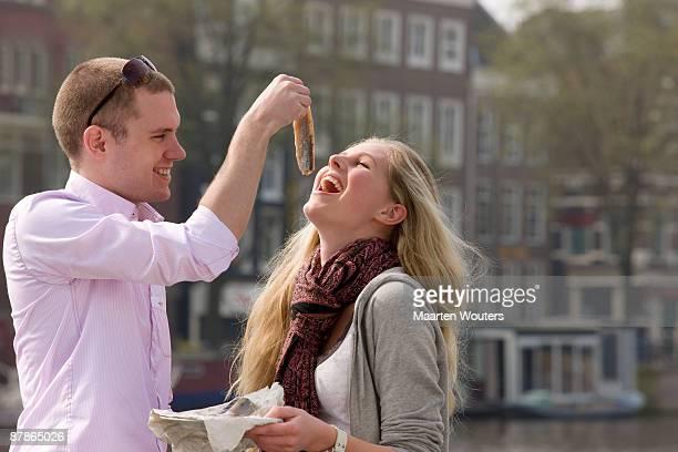 amsterdam tourist couple eating herring