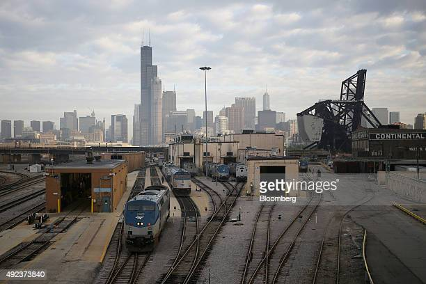 Amtrak locomotives sit parked at the 18th Street locomotive shop as the Willis Tower stands in the skyline of Chicago Illinois US on Wednesday Oct 7...