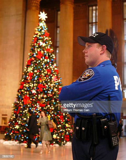 Amtrak Police Officer Bill Mooney stands guard near an escalator to a train during his patrol at 30th Street Station December 23 2003 in Philadelphia...
