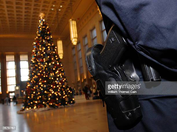 Amtrak Police Officer Eric J Wolf's handgun rests in his holster as he patrols 30th Street Station December 23 2003 in Philadelphia Pennsylvania US...