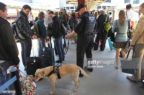 Amtrak police officer Joe Agnellino and his bomb detection dog 'Roxy' check passengers before they board a train at South Station