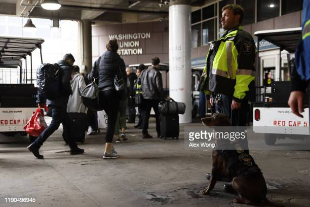 Amtrak Police officer Nicholas Spioch and his canine Silvia watch passengers passing by at Union Station November 27, 2019 in Washington, DC. The...