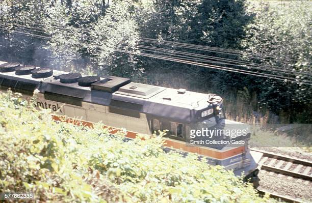 Amtrak train crossing a railroad bridge viewed from trees above the tracks 1966