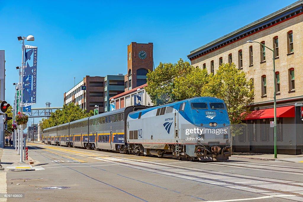 Amtrak train on street, Jack London Square, Oakland, California : Stock Photo