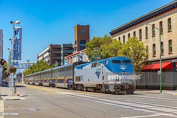 amtrak train on street, jack london square, oakland, california - oakland califórnia - fotografias e filmes do acervo