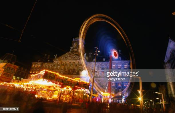 amusement park at night in front of illuminated koninklijk paleis (1865), dam square on queens day celebrations. - king's day netherlands stock photos and pictures