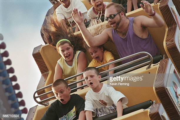 Amusement Park Goers Riding The Sea Dragon Roller Coaster