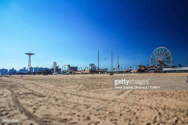 amusement park on beach against clear blue sky - coney island stock pictures, royalty-free photos & images