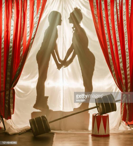 amusing loving couple. shadows of circus performers on curtain - circus stock pictures, royalty-free photos & images