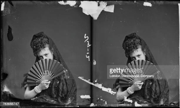Amy Angeloni posing with her face partly hidden by a fan London circa 1880