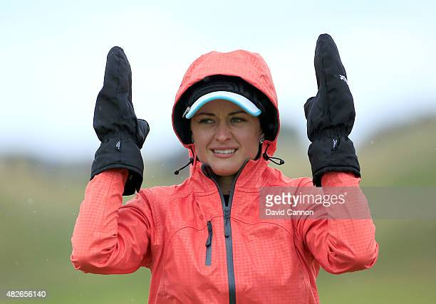 Amy Boulden of Wales sheltering from the elements after she had played her second shot at the par 5 17th hole during the third round of the 2015...