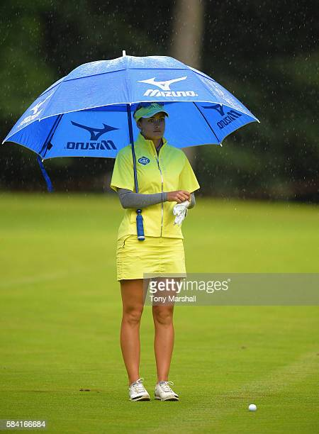 Amy Boulden of Wales shelters under an umbrella from a rain shower as she waits to play her second shot on the 3rd fairway during the Ricoh Women's...