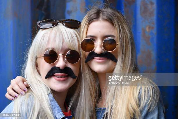 Amy Donnelly and Mackenzie Greene pose for a portrait as Beatles fans in costume attempt to break the Guinness World Record for the largest gathering...