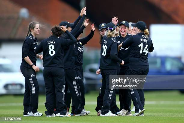 Amy Gordon of Surrey celebrates with her teammates after taking a catch during the Women's County Championship match between Surrey Women and...