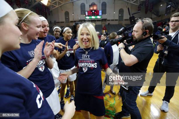 Amy Gutmann President of the University of Pennsylvania celebrates with players of the Penn Quakers after winning a game against the Princeton Tigers...