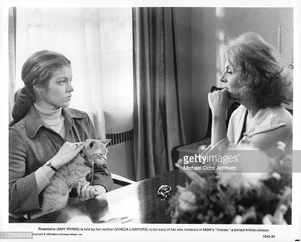Amy Irving with a cat on her lap talk with Viveca Lindfors in a scene from the film 'Voices' 1979