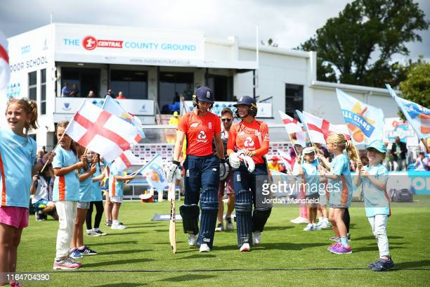Amy Jones and Danielle Wyatt of England make their way to the field to open the batting during the 2nd Vitality Women's IT20 at The 1st Central...