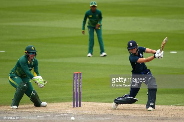 Amy Jones of England hits out while South Africa's Lizelle Lee looks on during the ICC Women's Championship 2nd ODI match between England Women and...