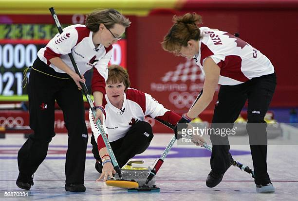 Amy Nixon and Christine Keshen of Canada sweep as Glenys Bakker delives the stone during the preliminary round of the women's curling between Great...