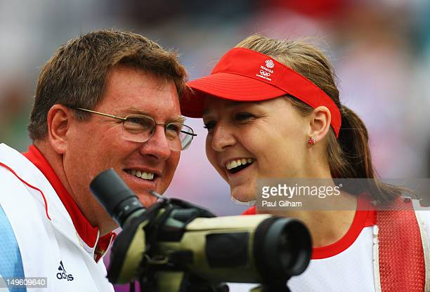 Amy Oliver of Great Britain smiles with her coach as she competes in her Women's Individual Archery 1/16 Eliminations match against Ika Yuliana...
