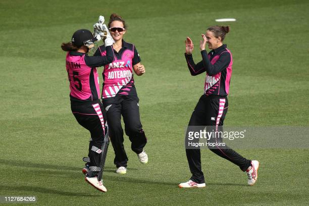 Amy Satterthwaite of New Zealand celebrates with Amelia Kerr and Katey Martin after taking the wicket of Priya Punia of India during game one of the...