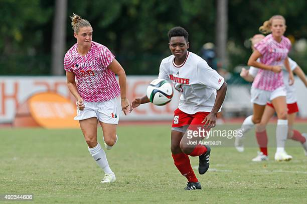 Amy Schmidt of the Miami Hurricanes and Ella Bonner of the North Carolina State Wolfpack chase a loose ball at midfield on October 11 2015 at Cobb...