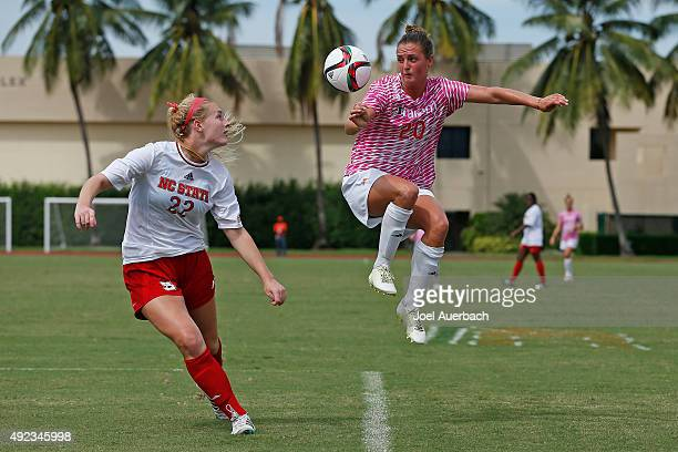 Amy Schmidt of the Miami Hurricanes attempts to head the ball past Cailyn Boch of the North Carolina State Wolfpack on October 11 2015 at Cobb...