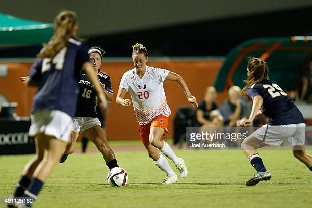 Amy Schmidt of the Miami Hurricanes carries the ball past a trio of Notre Dame Fighting Irish defends during first half action on October 2 2015 at...