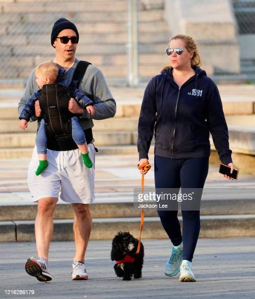 Amy Schumer and husband Chris Fischer take a walk in the park with their son Gene Fischer and the family dog on April 01 2020 in New York City