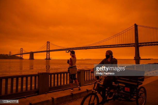 Amy Scott of San Francisco takes in the view from the Embarcadero as smoke from various wildfires burning across Northern California mixes with the...