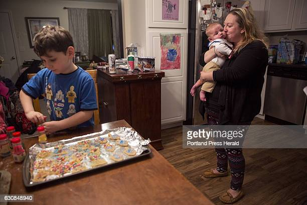 Amy Starr holds her youngest son Finn who is 3 months old as she watches her son Everett Rovin decorate Hanukkah cookies at their home in Gorham The...