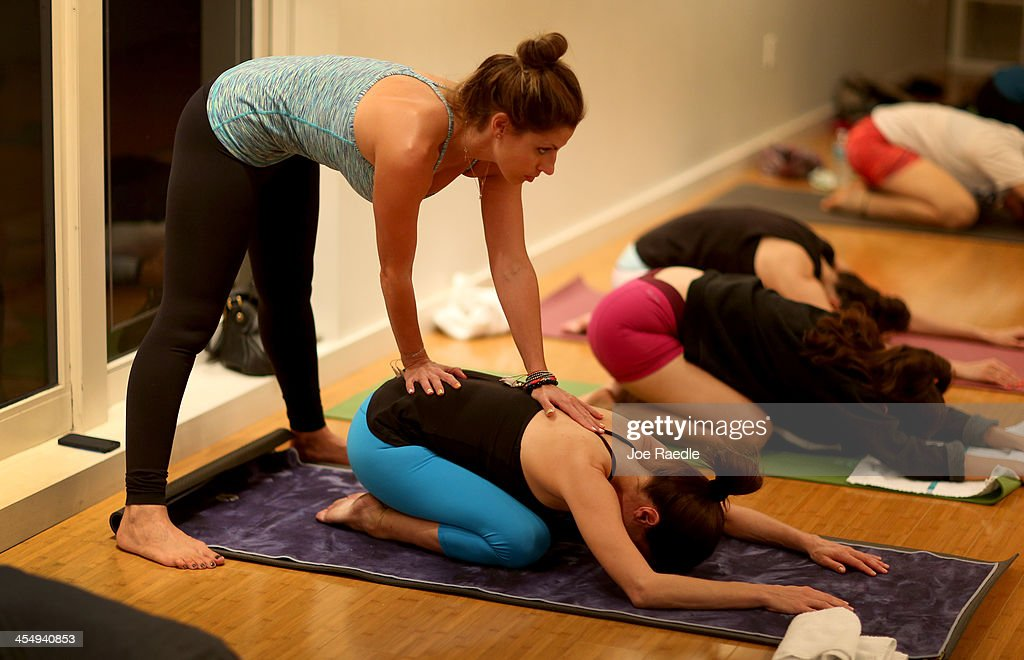 Amy Steiner (L) helps Paula Walker as she leads a yoga class while they both are dressed in Lululemon Athletica yoga clothes at the Green Monkey yoga studio on December 10, 2013 in Miami Beach, Florida. Lululemon Athletica, Inc. announced today that it is naming Laurent Potdevin as their new chief executive and said founder Chip Wilson will step down as chairman.