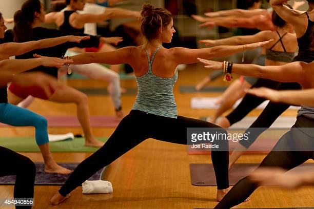 Amy Steiner leads a yoga class while dressed in Lululemon Athletica yoga clothes at the Green Monkey yoga studio on December 10, 2013 in Miami Beach,...