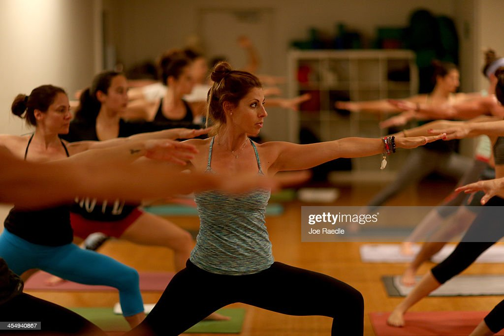 Amy Steiner (C) leads a yoga class while dressed in Lululemon Athletica yoga clothes at the Green Monkey yoga studio on December 10, 2013 in Miami Beach, Florida. Lululemon Athletica, Inc. announced today that it is naming Laurent Potdevin as their new chief executive and said founder Chip Wilson will step down as chairman.