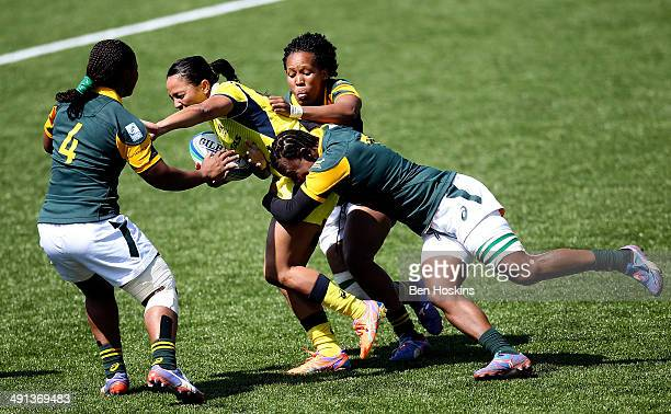 Amy Turner of Australia is tackled by Fundiswa Plaatjie and Coco Momoti of South Africa during the IRB Womens Sevens match between Australia and...